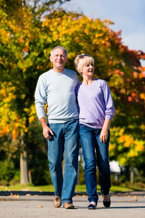 Man and woman, senior couple, having a walk in autumn or fall outdoors, the trees show colorful foliage photo