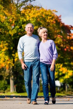 senioren wandelen: Man en vrouw, senior paar, met een wandeling in de herfst of najaar buiten, de bomen tonen kleurrijke gebladerte