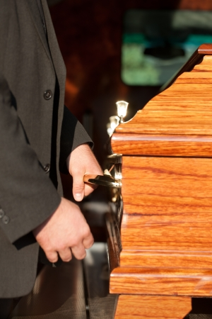 bearer: Dolor - Funeral with coffin on a cemetery, the casket carried by coffin bearer Stock Photo