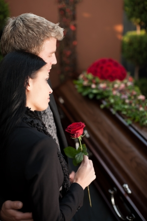 Morning man and woman on funeral with red rose standing at casket or coffin photo