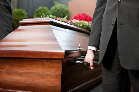 undertaker: Religion, death and dolor  - coffin bearer carrying casket at funeral to cemetery