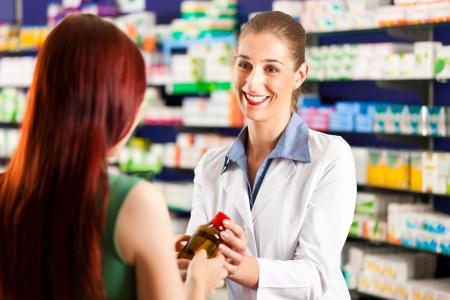 farmacia: Farmacista femmina consultazione di un cliente femminile nella sua farmacia