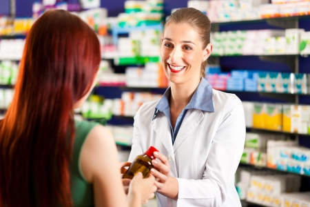 pharmacist: Female pharmacist consulting a female customer in her pharmacy