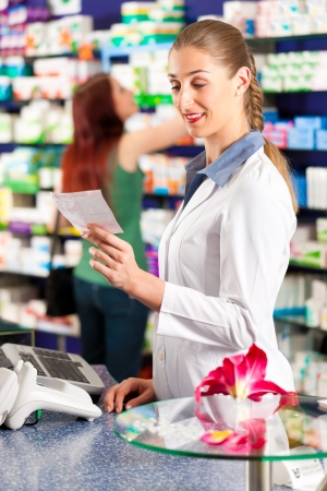 Female pharmacist is standing in her drugstore behind the counter and holds a prescription; in the background a female client is standing photo