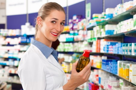 Female pharmacist is standing in her drugstore and holds a medicine bottle photo