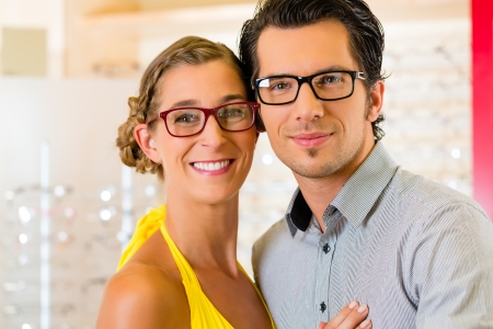 Young couple at optician in the store, they looking for glasses photo