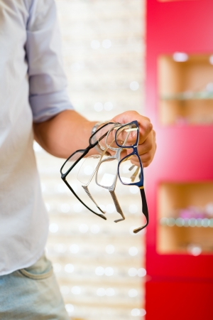 specialized: Young man at optician with glasses
