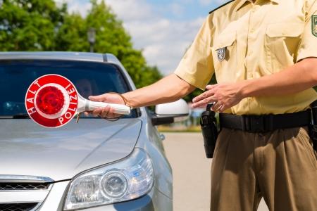 speeder: Police - policeman or cop in uniform stop car in traffic control
