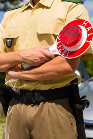 public sector: Police - policeman or cop in uniform stop car in traffic control