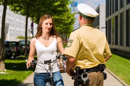 Police - young woman on bicycle with police officer in traffic control