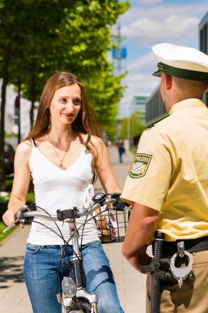 public service: Police - young woman on bicycle with police officer in traffic control