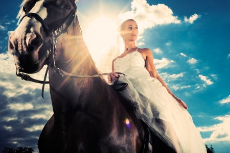 Young Bride in wedding dress riding a horse, backlit picture, dreamy mood photo