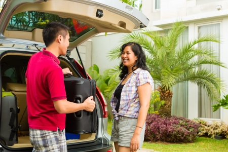 Asian couple packing car with suitcases for holiday and smiling Stock Photo - 16883592