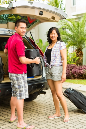 Asian couple packing car with suitcases for holiday and smiling photo