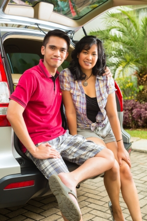 Asian couple is happy in front the car and ready to go on vacation photo