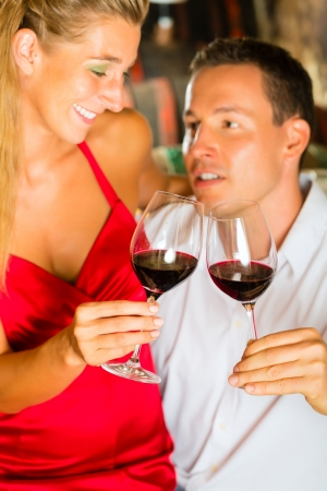 Couple - man and woman- tasting red wine in a cellar, in the background barrels can be seen photo