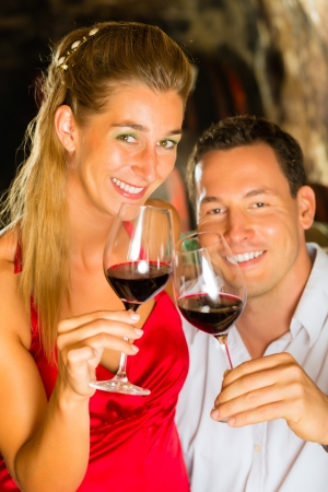 judged: Couple - man and woman- tasting red wine in a cellar, in the background barrels can be seen Stock Photo