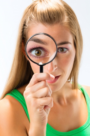 curiousness: Woman looking through magnifying glass or loupe