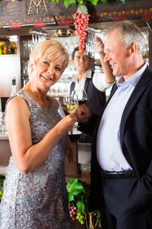 Senior couple in restaurant standing at bar with glass of wine in hand and having fun Stock Photo - 16883491