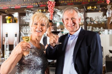 Senior couple in restaurant standing at bar with glass of wine in hand and having fun Stock Photo - 16883429