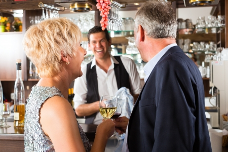 Senior couple in restaurant standing at bar with glass of wine in hand and having fun photo