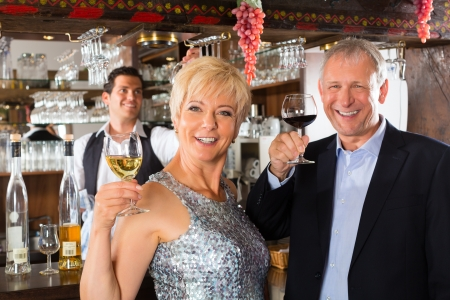 Senior couple in restaurant standing at bar with glass of wine in hand and having fun Stock Photo - 16883478