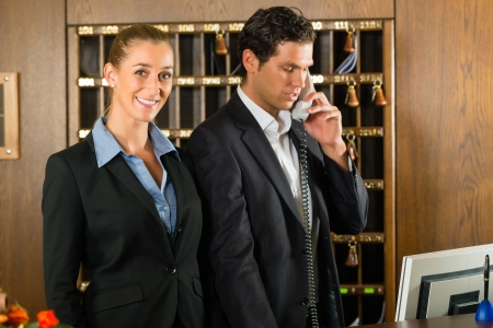 key cabinet: Reception in hotel - Man and woman standing at the front desk, man taking a call, woman holding a key in the hand and smiling Stock Photo