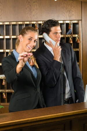 Reception in hotel - Man and woman standing at the front desk, man taking a call, woman holding a key in the hand and smiling Stock Photo - 16883577