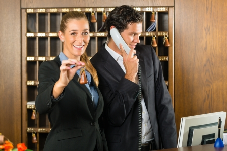 Reception in hotel - Man and woman standing at the front desk, man taking a call, woman holding a key in the hand and smiling photo