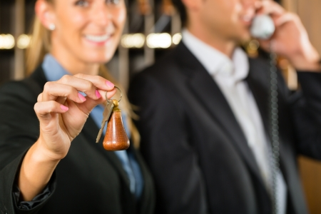 Reception in hotel - Man and woman standing at the front desk, man taking a call, woman holding a key in the hand and smiling Stock Photo - 16883809