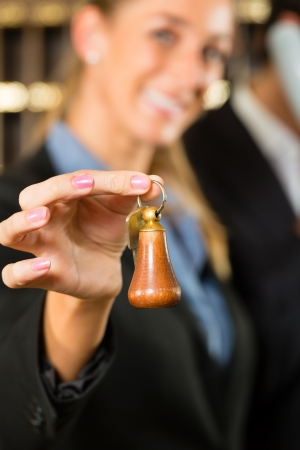 Reception in hotel - Man and woman standing at the front desk, man taking a call, woman holding a key in the hand and smiling Stock Photo - 16883804