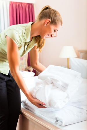 Maid doing room service in hotel, she is making up the beds photo