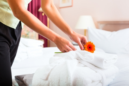 hotel service: Maid doing room service in hotel, she is making up the beds Stock Photo