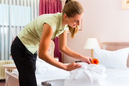 an attendant: Maid doing room service in hotel, she is making up the beds Stock Photo