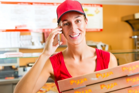 order delivery: Woman working as delivery girl in a pizza place holding several pizza boxes smiling Stock Photo