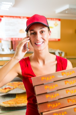 delivery service: Woman working as delivery girl in a pizza place holding several pizza boxes smiling Stock Photo