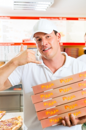 Man holding several pizza boxes in hand and asking you to order pizza for delivery photo