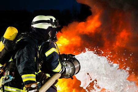 departamentos: Bombero - Los bomberos extinguen un incendio grande, est�n de pie con ropa de protecci�n delante de la pared de fuego