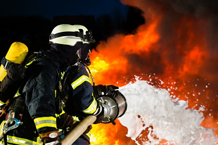 fireman: Firefighter - Firemen extinguishing a large blaze, they are standing with protective wear in front of wall of fire Stock Photo