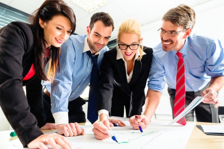determine: Four professionals in office in business attire having strategy meeting to determine the future of company Stock Photo