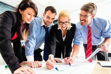 Vier Profis im B�ro in Business-Kleidung mit Strategie-Meeting, um die Zukunft des Unternehmens bestimmen