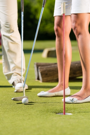 woman only: People, man and woman, only feet, playing miniature golf on a beautiful summer day