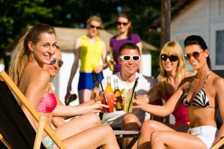 fiesta amigos: La gente en la playa bebiendo una fiesta, los amigos que tintinean los vidrios con los cocteles y cervezas que se divierten