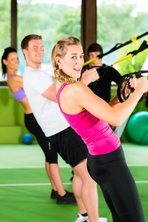 fitness club: Group of people exercising with suspension trainer in fitness club or gym