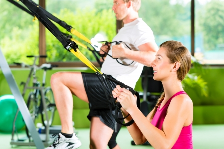 Group of people exercising with suspension trainer in fitness club or gym  photo