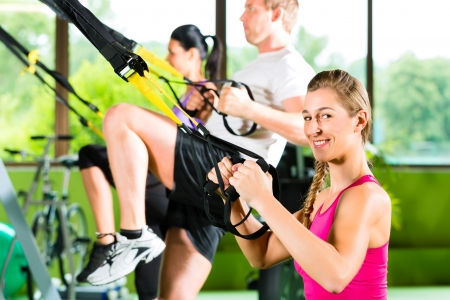suspension: Group of people exercising with suspension trainer in fitness club or gym