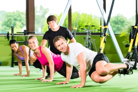 dynamic activity: Group of people exercising with suspension trainer in fitness club or gym