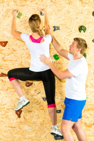 Woman and man climbing at climbing wall and training the body photo