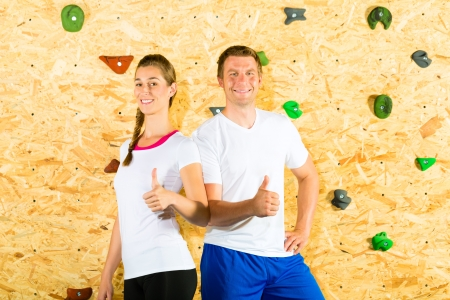 Woman and man standing at climbing wall and smiling photo