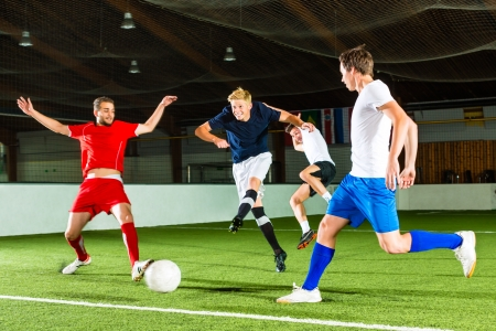indoor soccer: Men team playing football or soccer indoor and trying to score a goal Stock Photo